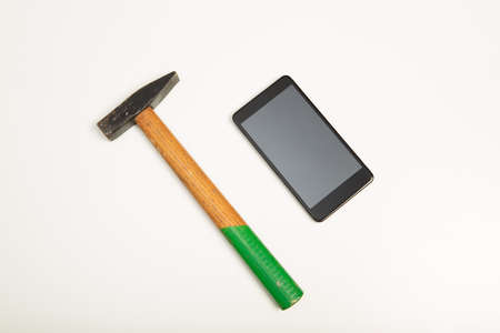 Studio shot high-angle close-up view of a black smartphone next to a hammer on white background for copy space