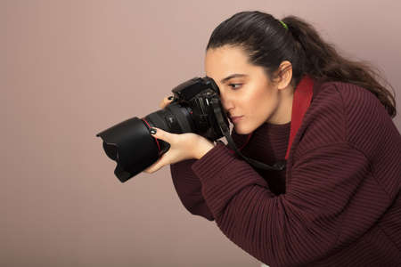 Young woman photographer taking a photo with a professional DSLR and lens bending forwards as she focuses on her subject in a side view Stock Photo - 96486644