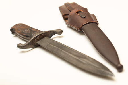 Old dagger with a worn leather sheath to carry the weapon isolated on a white background with copy space Stock fotó