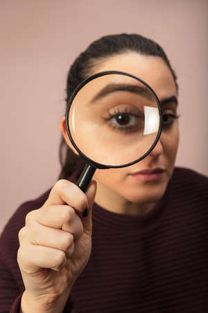 Woman searching for clues or conducting an investigation or search peering through a handheld magnifying glass , what makes his eye seem bigger Imagens