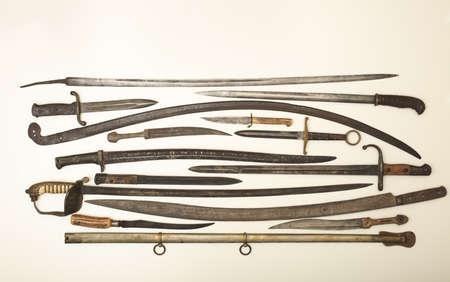 Vitrine met oude historische zwaarden en messen op een witte achtergrond in een expositie in een museum of een collectorshowcase