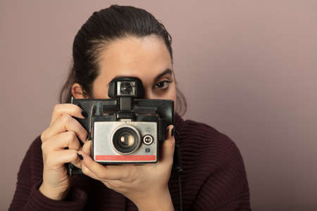 Young woman focusing on the viewer and taking picture with a vintage camera 스톡 콘텐츠
