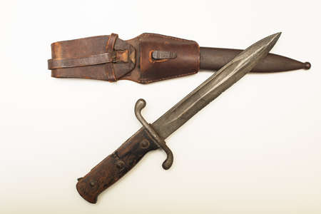 Old dagger with a worn leather sheath to carry the weapon isolated on a white background with copy space Stock Photo