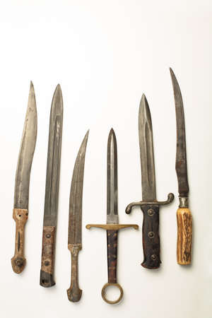 Collection of different vintage knives and daggers with a variety of shapes of blade and hilt or handle laid out in a neat row on white with copy space Stock Photo