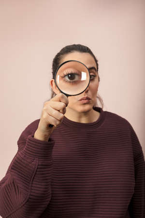 Woman searching for clues or conducting an investigation or search peering through a handheld magnifying glass , what makes his eye seem bigger Banco de Imagens