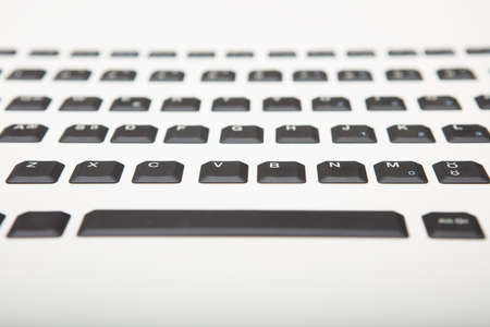 Low angle view of a qwerty alphanumeric computer keyboard with black keys on silver gradient to white with selective focus to the part of center keys Imagens - 97398798