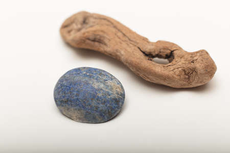 Lapis lazuli  is a deep blue metamorphic rock used as a semi-precious stone on a white background with old wood Stock Photo