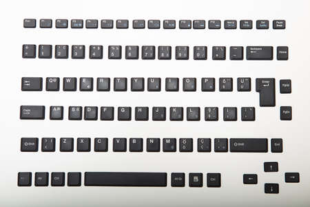 Loose alphanumeric covers for the keys on a computer keyboard on a white or light silver background viewed from overhead centered in the screen with surrounding copy space