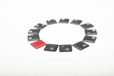Neat circle of loose grey keyboard key covers with a single red cover inserted in the line conceptual of leadership, diversity and individuality low angle over white with copy space