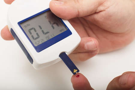 Man with diabetes using a portable digital glucose meter drawing up a sample of blood from a pinprick on his fingertip. Data at HIGH blood sugar level