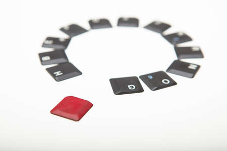 Circle of loose alphanumeric computer keyboard key covers with one single red one in the foreground in a concept of individualism, diversity, leadership or being unique viewed low angle on white