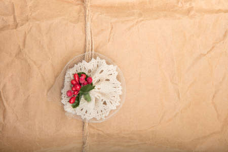Close up view of a gift in crumpled vintage brown recycle paper tied with string and attached decoration with red berries on a white background Stock fotó