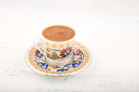 A vintage cup of Turkish black coffee on a saucer placed in the wooden table, with copy space, viewed from high angle