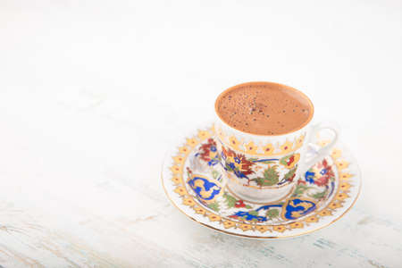 Vintage cup of Turkish coffee on a saucer over wooden surface background, viewed high angle with copy space to the side