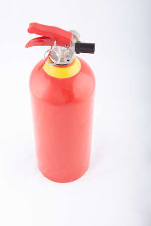 Top down view on a portable red fire extinguisher on a white floor with focus to the nozzle, High resolution picture Imagens
