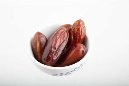 Dried date fruit in bowl on white background , high angle view high quality image Standard-Bild