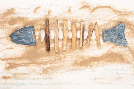 Decorative hand-crafted fish formed of stones and wood on scattered beach sand over a white and blue wooden   background for nautical or marine concepts Stock fotó