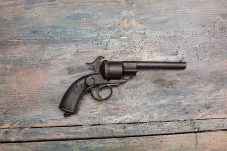 Historic gun in a museum exhibit or collectors showcase displayed on a wooden background in a close up shadowy view with copy space