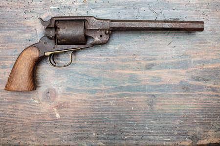 Pistola histórica en una exhibición de museo o vitrina de coleccionistas que se muestra sobre un fondo de madera en una vista en sombras con espacio de copia
