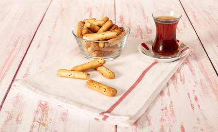 Crunchy grissini with Turkish tea ready to serve on cloth napkin high angle view on wooden table