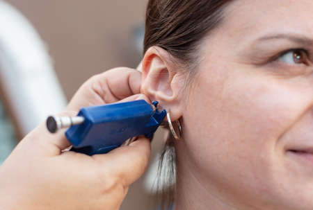 Woman having ear piercing process with special piercing gun in beauty center by medical worker, cropped close up view