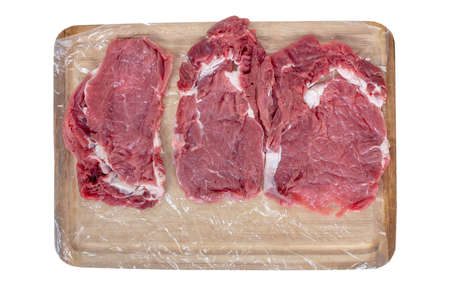 Fresh raw beef steaks   over opened vacuum packed on wooden cutting board on white background , top view Stok Fotoğraf