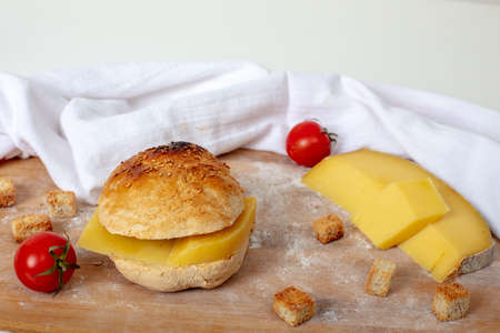 Freshly baked homemade sandwich with  fabric on  wooden cutting board with   cherry tomatoes , traditional cheddar and flour  High angle view with Reklamní fotografie