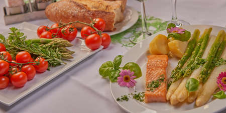 coalfish: Fish fillet steamed served with asparagus and potato, bot on a table decorated Stock Photo