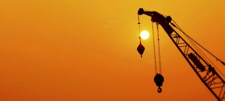 Hoisting cranes working on beautiful cloudy sky with orange sunset and rays of light background.