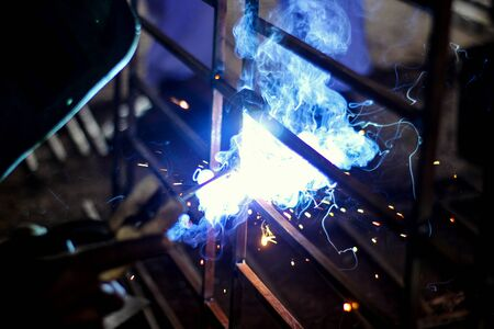 Metal welding with sparks and smoke on dark background.