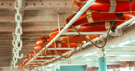 Line of lifebuoy ring floatation inside a traveler ship . Blurry background with copy space for text . Banco de Imagens