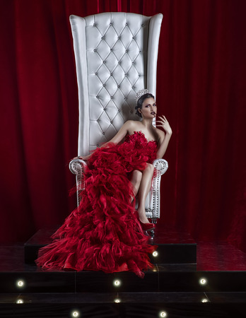 girl in a red dress and a crown on the throne Stockfoto