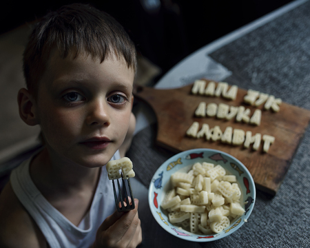 fundamentals: little boy teaches letters and eats pasta