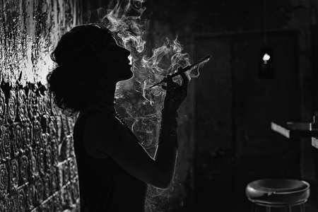 cigar shape: the dark silhouette of a woman smoking black and white