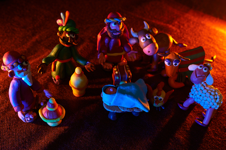 many plasticine figures on the theme of Christmas with beautiful orange blue lighting Stock Photo