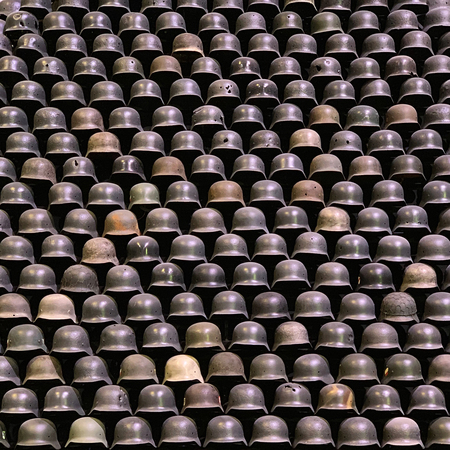 pyramid made up of a large number of military helmets Stok Fotoğraf