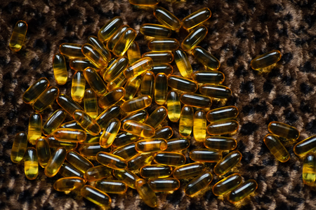 many capsules of gold color lies on the leopard skin in various forms