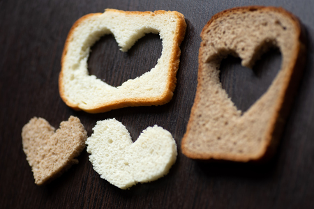 hearts carved from a piece of bread on a dark wooden table