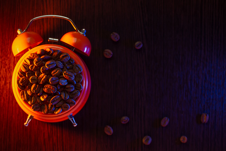 orange alarm clock with coffee beans on a wooden table