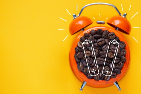 coffee beans in orange alarm clock on bright yellow background and batterys Stock Photo