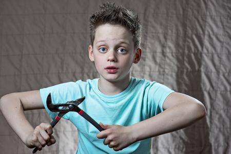 ein Junge mit einem Schraubenschlüssel und überraschten Augen repariert etwas