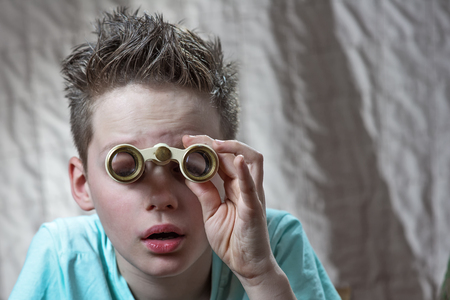 surprised teen boy emotionally looking through theater binoculars