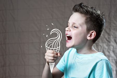 boy in a light t-shirt eating painted ice cream from which flying spray Stock Photo