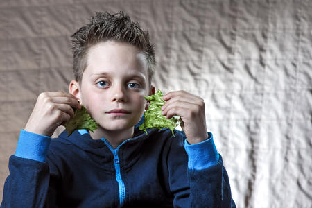 boy in a blue jacket holding two sheets of salad