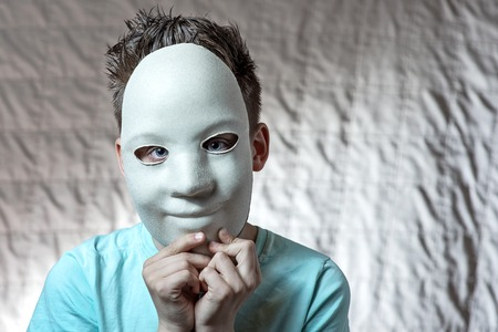 boy in a light t-shirt leaned against the face of a white mask
