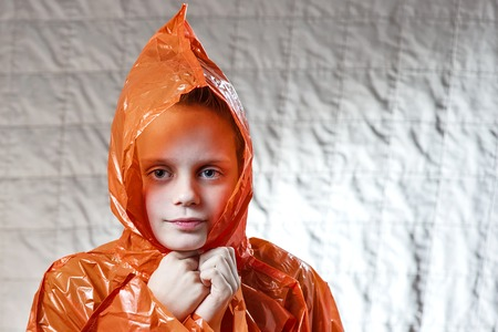 boy in a bright orange raincoat took shelter from the rain