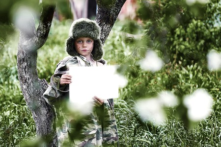boy in a camouflage uniform and a hat with earflaps stands in an Apple orchard with a clean white sheet