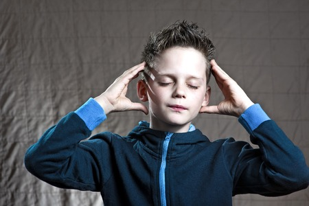 the boy's head ached and he put his hands to his temples