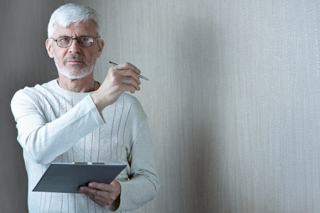 a gray-haired man in light clothes and glasses enters into a contract on paper Stock Photo