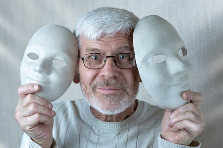 portrait of a cheerful gray-haired man with two theatrical masks